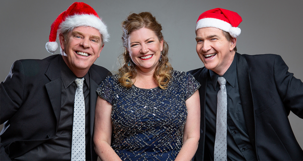 Three happy performers wearing santa hats