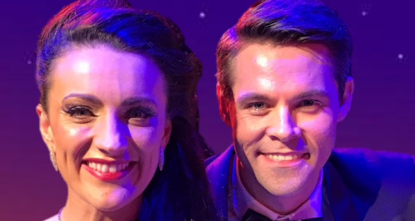 a male and female singer smiling and bathed in purple stage light