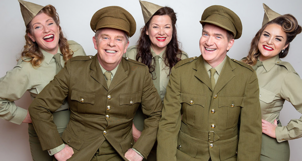 Five actors smiling wearing 1940's army uniforms