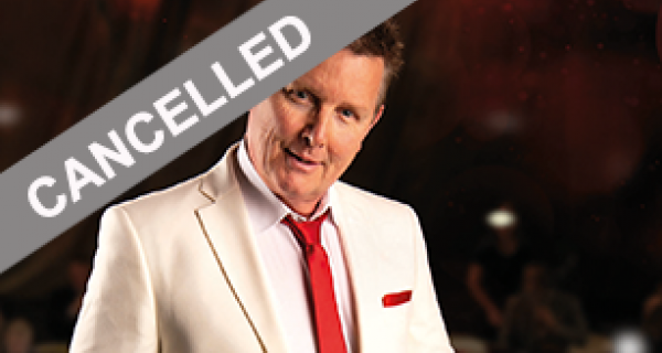Singer, Tom Burlinson wearing a white dinner jacket and red tie