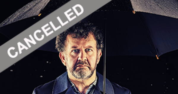 Bearded man looking sad and standing under a black umbrella