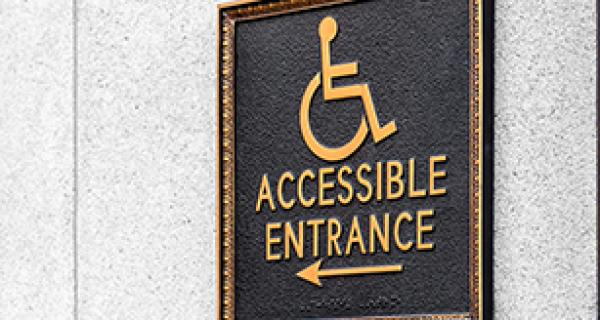 Plaque on exterior wall showing a wheelchair symbol and arrow to entrance