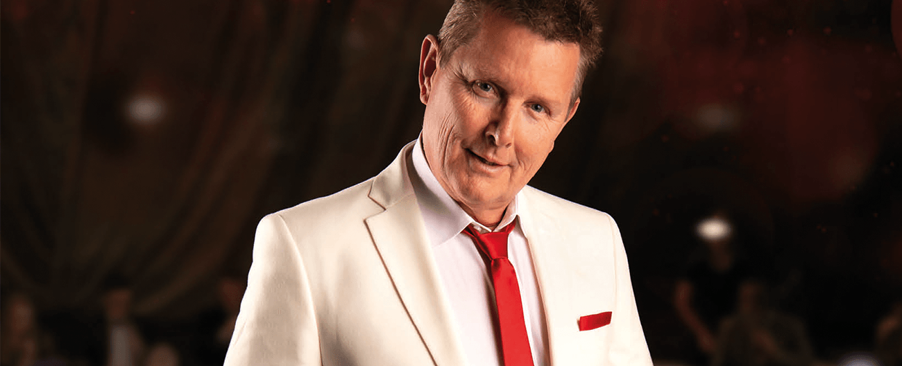 Tom Burlinson standing in a white jacket, black pants and red tie against a dark background